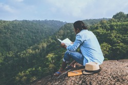 Asian man travel relax in the holiday. seats relax read books on rocky cliffs. On the Moutain. In Thailand