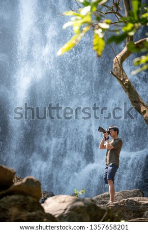 Asian man traveler and photographer using digital camera taking photo at waterfall. Travel lifestyle or nature photography concepts