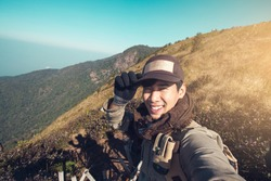 Asian man traveller happy smiling take a selfie on the mountain.