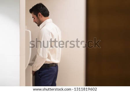 Asian man urinating in toilet; portrait of Indian man using water closet, WC for peeing; concept of health care, prostate cancer, urethritis, UTI or urinary tract infection; Asian adult man model