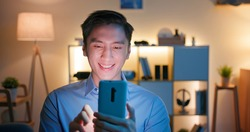 asian man use smart phone and watches something interesting on social media happily at home in the evening