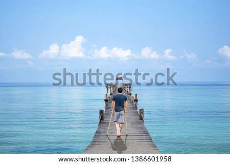 Asian man used wooden crutches walks on  bridge pier boat in the summer sea and the bright sky at Koh Kood, Trat in Thailand. #1386601958