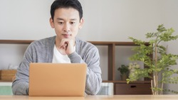 Asian man using a computer in the living room