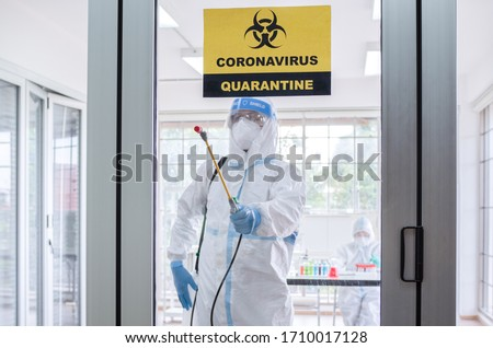 Asian man wear personal protective suits or PPE, goggles, mask, and gloves making disinfection and decontamination on quarantine room with coronavirus alert sign. Covid-19 and disinfection concept