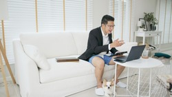 Asian man wearing a suit or business wear on top and sweatpants or boxers on bottom. Businessman video conference using laptop and tablet online meeting.Working from home and Working remotely.