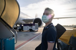 Asian man wearing face mask walks to stair entering airplane, parking at remote bay located outside terminal in airport. Male passenger traveling by plane transportation during covid19 virus pandemic.