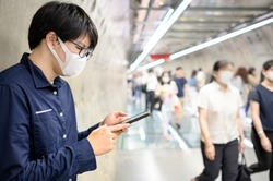 Asian man wearing surgical face mask using smartphone in subway tunnel with crowded people walking. Wuhan coronavirus (COVID-19) outbreak prevention in public area. Health care and medical concept