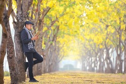 Asian man wearing sweater reading the book while leaning on the yellow leaves ginko tree in the park during autumn season with copy space