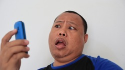 Asian man with bald hair is on the phone, with an old telephone with strange expression
