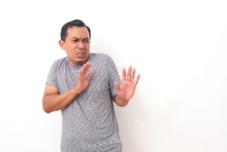 Asian man with disgusted expression repulsing something. Disgust concept. Emotional man. Human emotions, facial expression concept. Isolated on white background