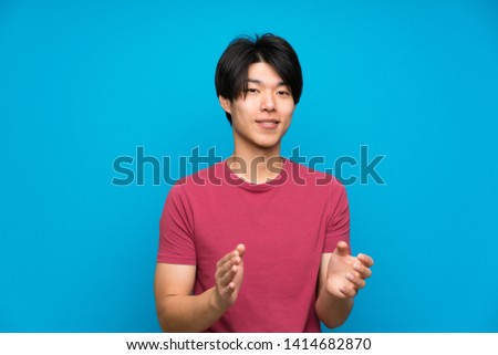 Asian man with red shirt over isolated blue wall applauding #1414682870