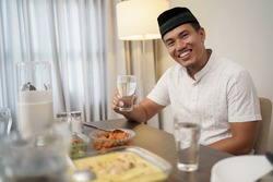 asian man with traditional muslim clothes breakfasting dinner at home