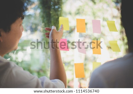 asian man & woman discussing creative idea with adhesive notes on glass wall at workplace. Sticky note paper reminder schedule at office. business, brainstorming, creativity concept #1114536740