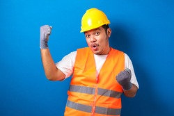 Asian man worker wearing safety helmet lookis happy celebrating his victory by clenching his fists against blue background