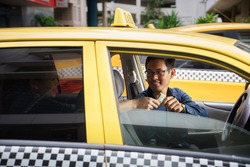 Asian man working as taxi driver in yellow car, with female client paying cash and leaving