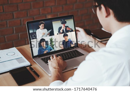 Asian man working from home use Smart working and video conference online meeting with Asian team using laptop and tablet online in video call for new projects