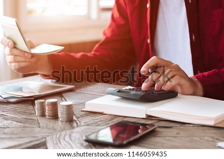 asian man working with calculator to calculate numbers. expenses calculator, payments costs with paper notes, payments table. Financial and Installment payment concept. Saving concept