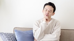 Asian man worries in the living room