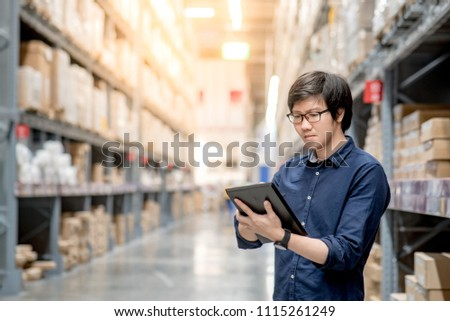 Asian manager man doing stocktaking of products in cardboard box on shelves in warehouse using digital tablet and pen. Male professional assistant checking stock in factory. Physical inventory count. #1115261249