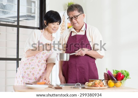 Asian mature couple cooking food at kitchen. Seniors living lifestyle at home.