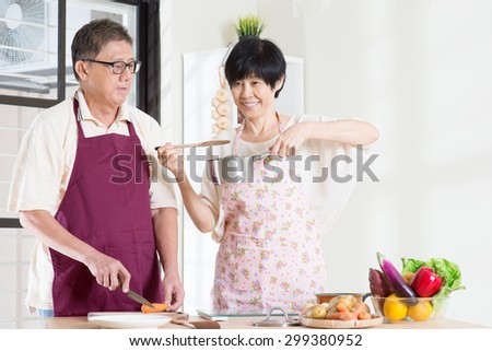 Asian mature couple cooking meal at kitchen. Seniors living lifestyle at home.