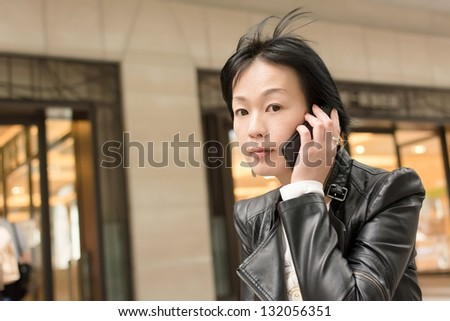 Asian mature woman use smart phone, closeup portrait.