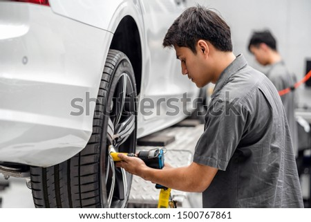 Asian mechanics checking the car wheels at maintainance service center for in showroom which is a part of showroom, technician or engineer professional work for customer, car repair concept