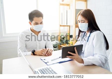 Asian Medical healthcare clinic doctor examining diagnosing male patient using tablet wearing surgical mask protection infection disease, working at home modern office technology computer laptop