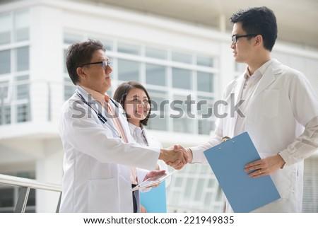 Asian medical team of doctors shaking hands inside hospital building
