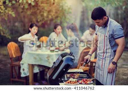 Asian men are cooking a barbecue for friends