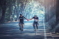 Asian men are cycling road bike in the morning and share out water to each other