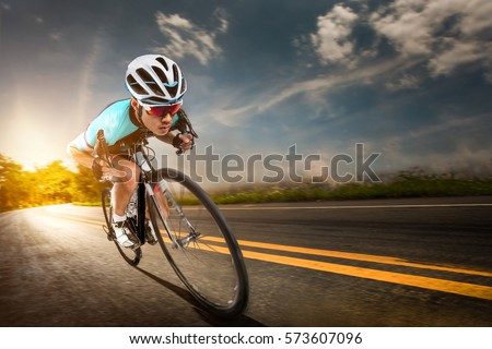 Asian men are cycling road bike in the morning.downhill