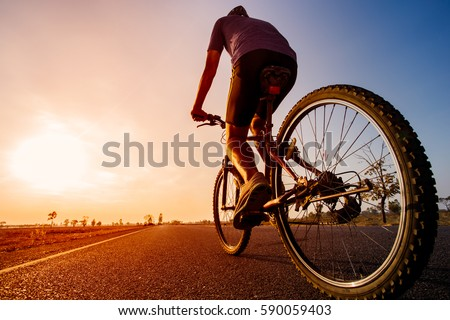 Asian men are cycling road bike in the the sunset