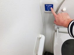 Asian men hand pressing blue flush button sign at the air plane lavatory to clean after use. Interior toilet design to match with small space inside the aircraft.