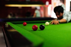 Asian men playing snooker,The player is aiming to shoot the red snooker ball,Hands on a green snooker table