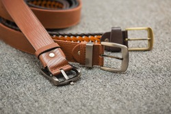 Asian men's vintage belt stylish, placed on a carpeted gray carpet on the floor.