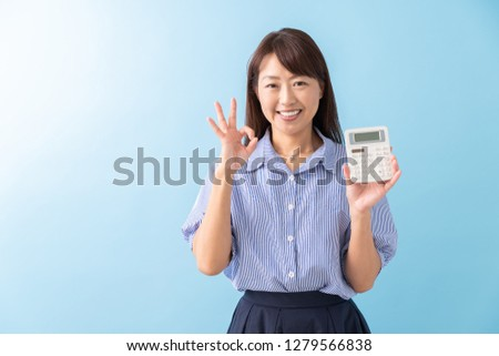 Asian middle age asian woman of the smile having an electronic calculator
