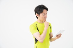 Asian middle age man who plays sports, tablet computer ,think,