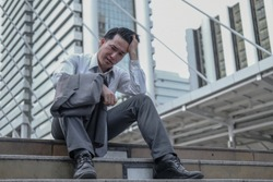 Asian middle aged businessman jobless due to economic recession make him feeling very stress and depressed. Impact of economic recession concept.