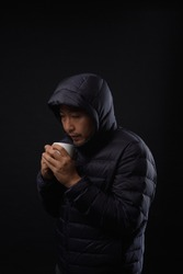 Asian middle aged man in anorak  holding cup drinking hot water to get warm on black background. Homeless concept.