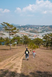 Asian mom and kid hiking near Lang Biang mountain in Dalat, Lam Dong, Vietnam.