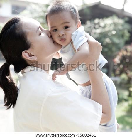 Asian mom kissing her son