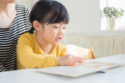 asian mom reading a book for daughter