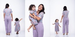 Asian Mother and Caucasian Daughter stand and wear same purple blouse pant dress together. Little girl hold mom hand and smile with love. White background isolated