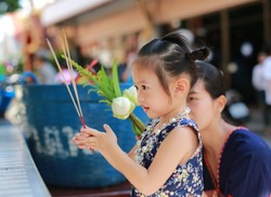 Asian mother and child girl in traditional songkran festival dress holding incense pay respect