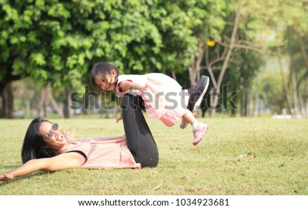 Asian mother and daughter are playing and laughing together with fully happiness moment in the green park and pink blossom, concept of love and relation in family lifestyle. #1034923681