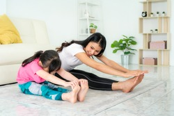 Asian Mother and daughter doing fitness exercises in living room at home to maintain physical and mental health and wellbeing get exercise into your daily routine while social distancing.