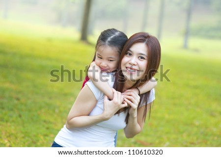 Asian mother and daughter having fun in park