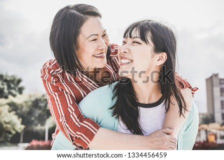 Asian mother and daughter having fun outdoor - Happy family people enjoying time togehter around city in Asia - Love, parenthood lifestyle, tender moments concept - Focus on faces #1334456459