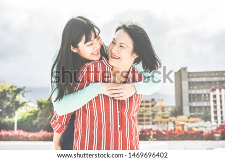 Asian mother and daughter having fun outdoor - Happy family people enjoying time togehter around city in Asia - Love, parenthood lifestyle, tender moments concept - Main focus on girl face #1469696402